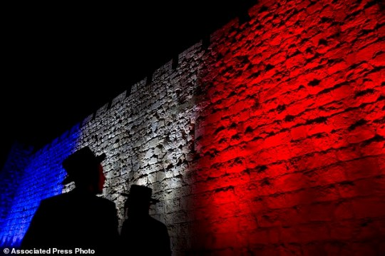 FILE - In this Sunday, Nov. 15, 2015 file photo, two Ultra-Orthodox Jews look at Jerusalem's Old City walls illuminated by the colors of the French national flag in solidarity with France after attacks in Paris, in Jerusalem.  Jewish immigration to Israel from western Europe has reached an all-time high as a result of a rise in anti-Semitic attacks, a leading nonprofit group said Thursday, Jan. 14, 2015. The vast majority, close to 8,000, came from France where a rise in anti-Semitic attacks has shattered the sense of security of the world's third-largest Jewish population. (AP Photo/Ariel Schalit, File)